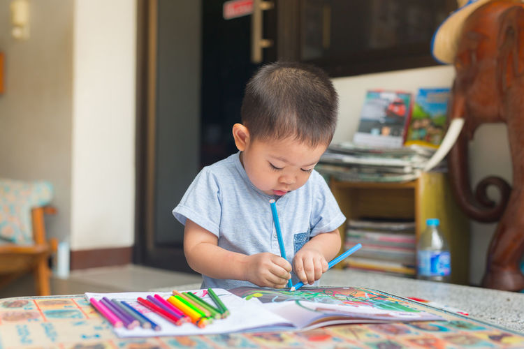 the boy is painting at his is home school. Attention Baby Japanese  Learning Paint Paint Brush Thailand Activity Adorable Book Childhood Chinese Colorful Pencils Creative Day Dirty Education Hobby Home School Infant Portrait Ready-to-eat Real People Toddler  Training
