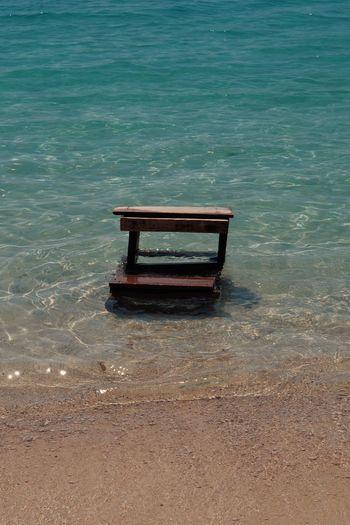 Empty bench on sea shore