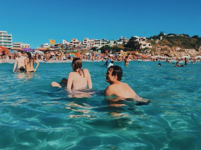 People enjoying in swimming pool against sea