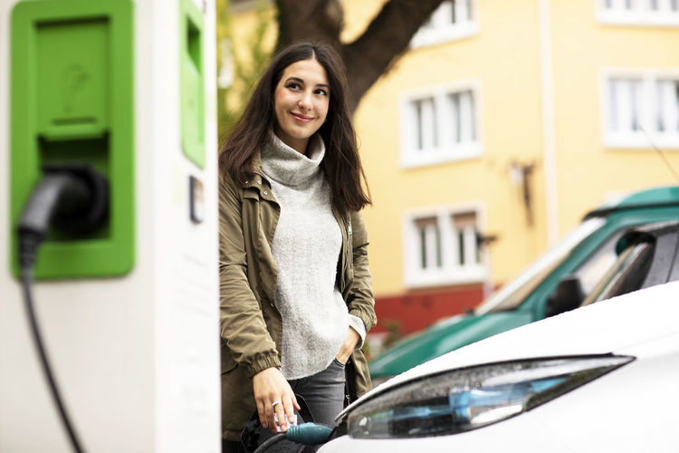 Portrait of smiling young woman standing in car