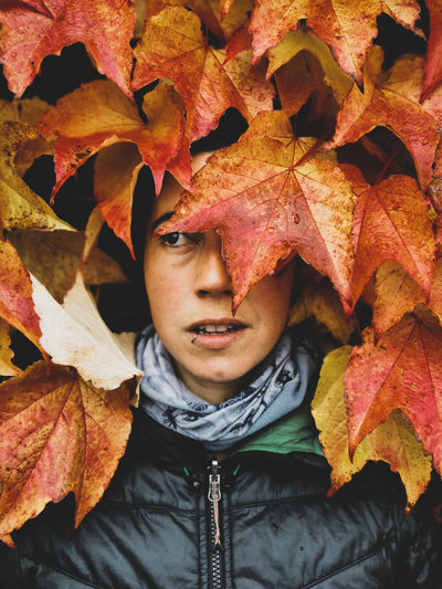 Close-up portrait of young woman with autumn leaves