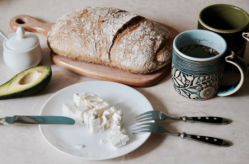 Breakfast, food, bread, toasts, knife and fork, cutting board, wooden, avocado, healthy, still life food, cheese, feta, cup, coffee, salt, mobile phone, top view, lifestyle, nutrition, organic food, honey, whole grains, sesame, seeds, tasty, eating, home, homemade, kitchen ware Food And Drink Food Freshness Table No People Bread Plate Healthy Eating Bowl Indoors  Breakfast Ready-to-eat Day Close-up Sliced Bread Abocado Toast Kitchen Utensils