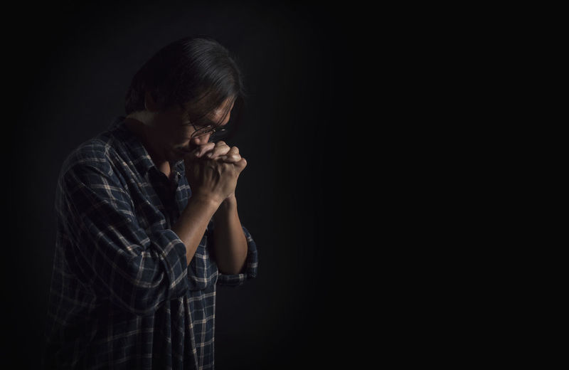 Prayer to God That is the anchor of the mind, faith and hope. One Person Black Background Studio Shot Indoors  Hand Waist Up Sadness Emotion Side View Copy Space Portrait Human Hand Young Adult Headshot Head In Hands Adult Human Body Part Casual Clothing Dark Profile View Hands Covering Mouth Depression - Sadness Hopelessness Contemplation Obscured Face