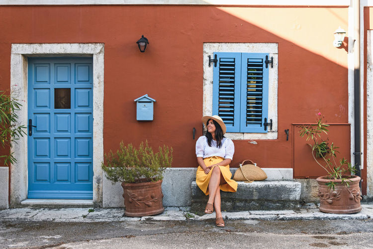 Young woman in summer outfit sitting on bench in front of colorful house.
