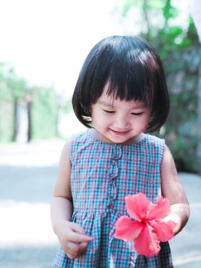 Cute Girl Holding Flower While Standing On Footpath