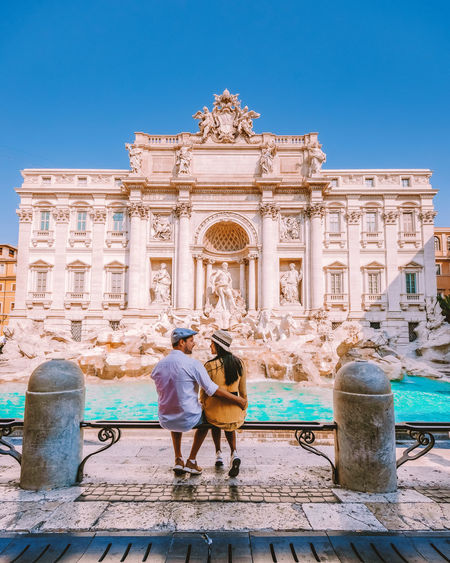 Rear view of couple in front of historical building