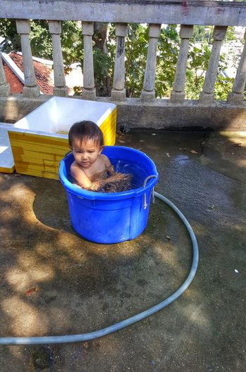 High angle view of shirtless boy sitting in bucket in terrace