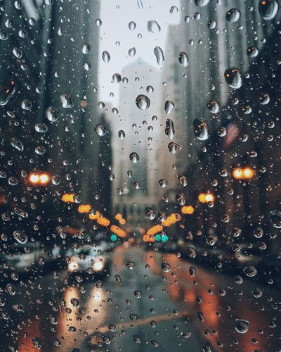 Car on street seen through wet car window during monsoon