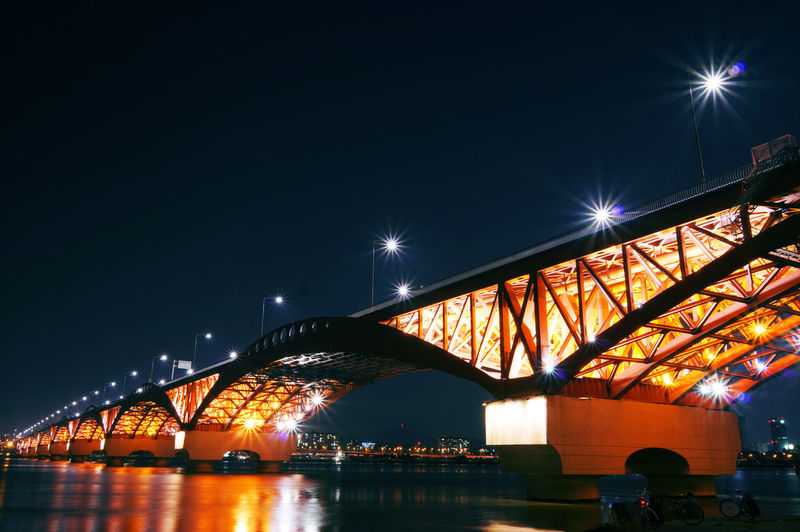 Illuminated bridge over river in city against sky at night
