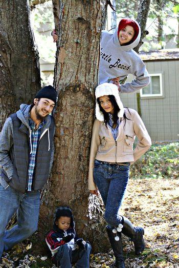 Portrait of happy friends standing by tree trunk