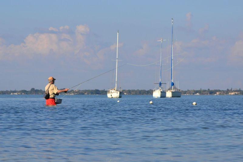 Rear view of a man fishing at calm sea