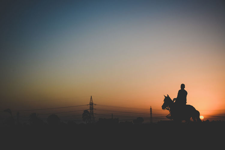 Silhouette man riding horse at desert against sky during sunset