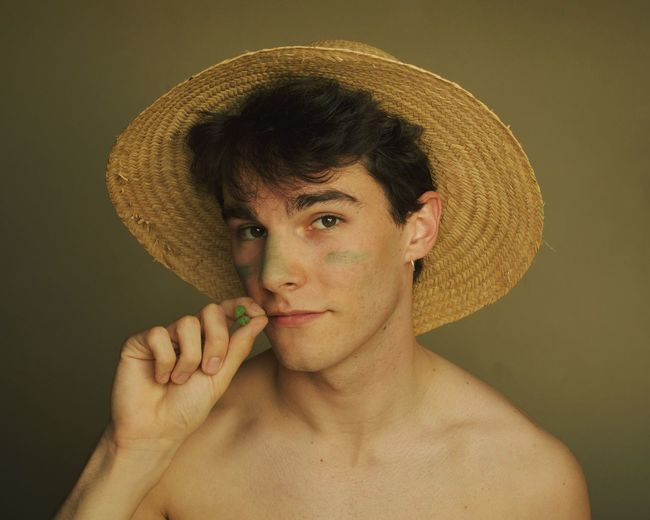 Portrait of shirtless man holding hat against gray background