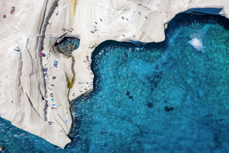 Aerial view of people on land by sea