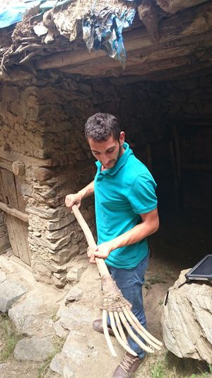 Full Length Of Man Holding Work Tool While Standing At Old Ruin
