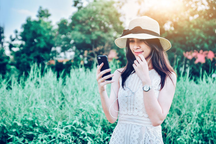 Young woman using mobile phone while standing on plants