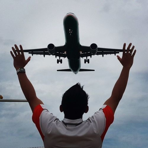 Man Looking At Flying Airplane While Raising Hands