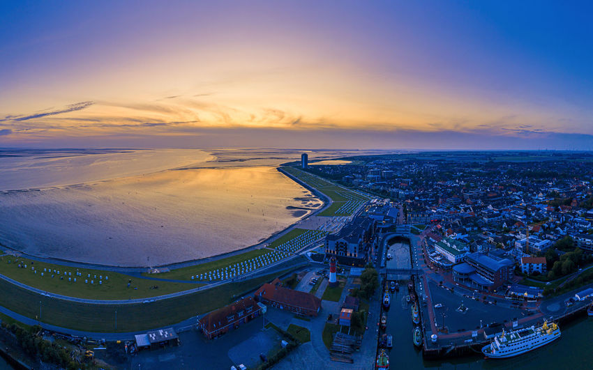 High angle view of sea by buildings against sky during sunset