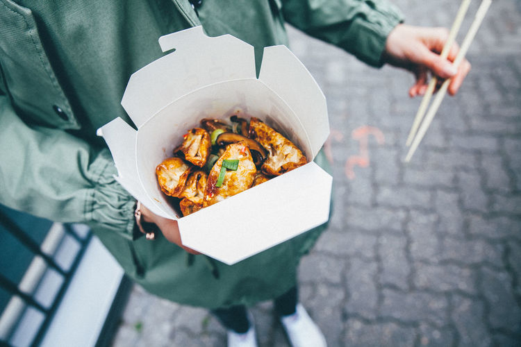 Midsection Of Person Holding Street Food On Sidewalk
