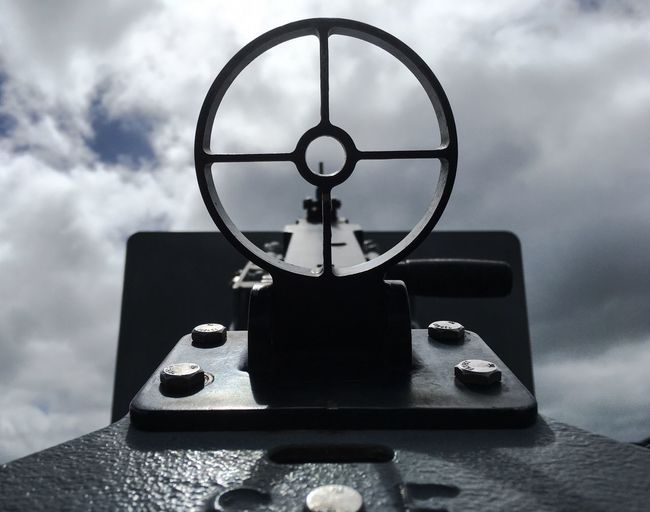Low angle view of old machine gun at hickam housing against cloudy sky