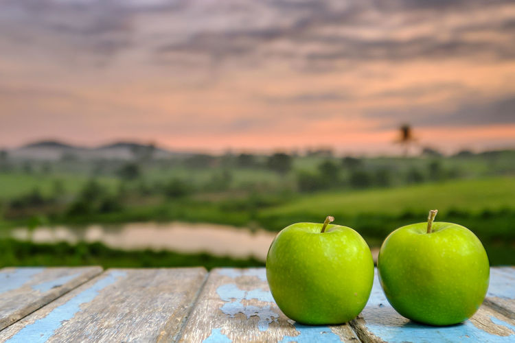 Two apples on wooden table in the sunlight with a blurred nature background. Apple - Fruit Beauty In Nature Close-up Day Focus On Foreground Food Food And Drink Freshness Fruit Granny Smith Apple Green Color Healthy Eating Nature No People Outdoors Sky Sunset Table Wood - Material