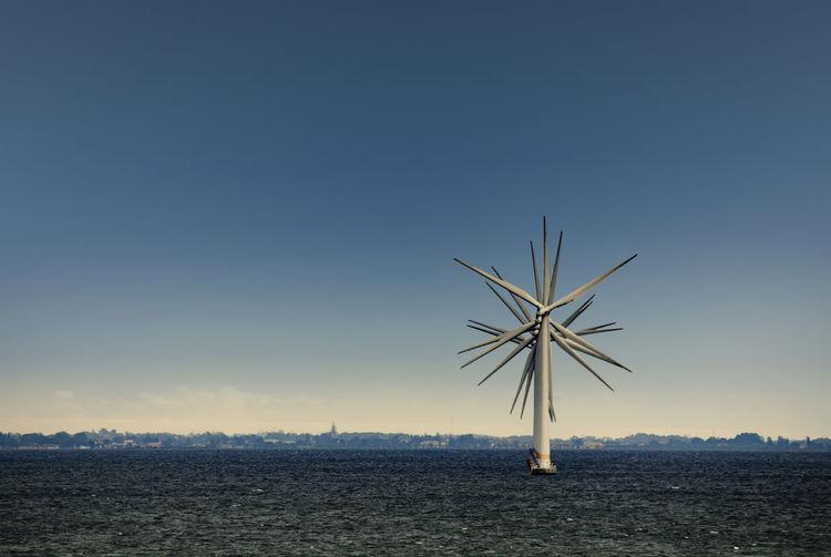 Windmills in sea against blue sky