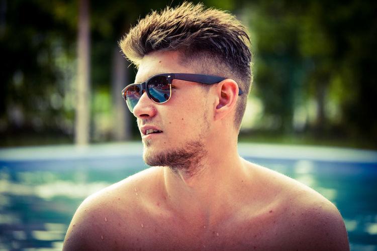 Shirtless man wearing sunglasses in swimming pool