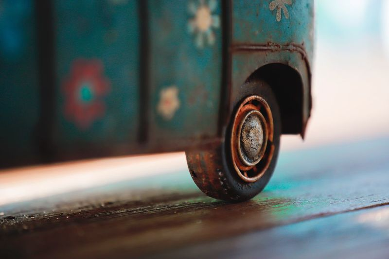 Close-Up Of Rusty Toy Car On Wooden Table
