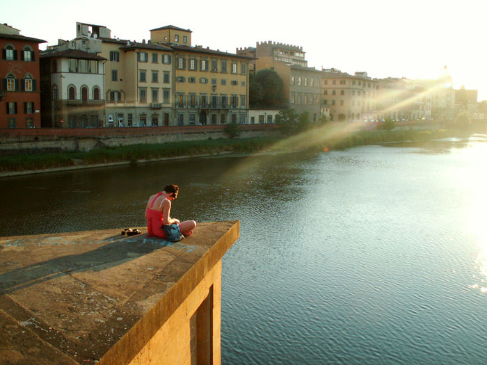 Man sitting by canal against buildings in city