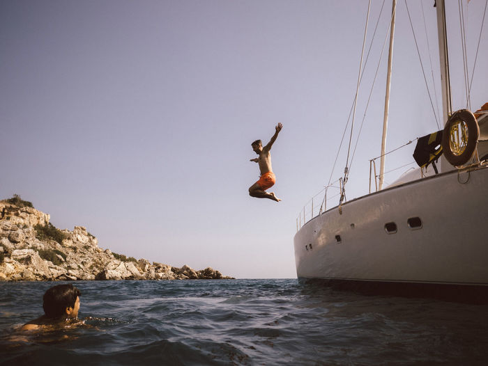 Man jumping in sea against clear sky