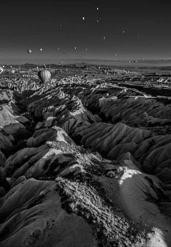 Scenic view of dramatic landscape with hot air balloon at cappadocia