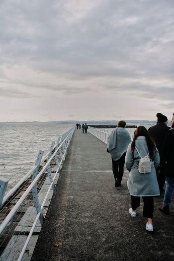 Rear view of people walking on sea shore against sky