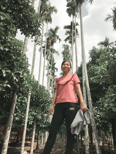 Low angle portrait of smiling young woman on palm trees
