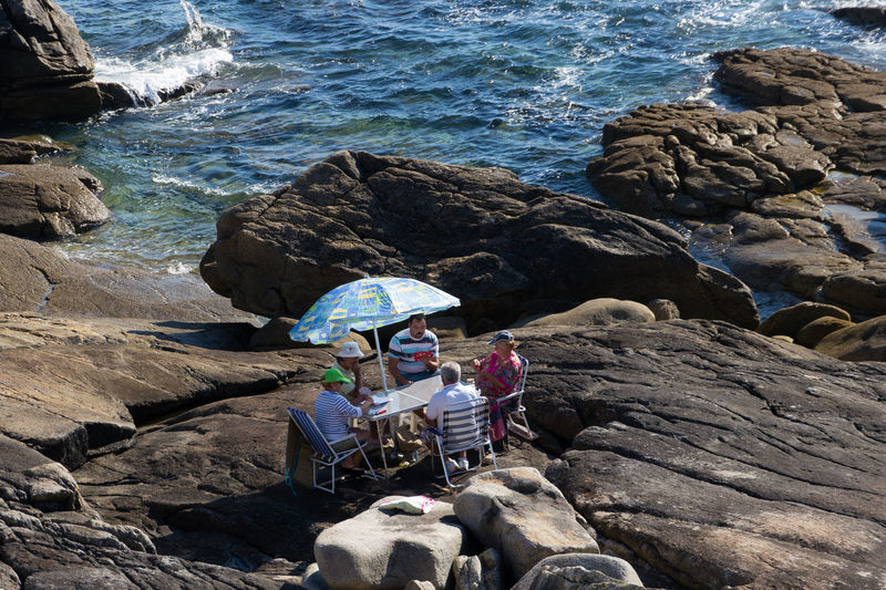 Card players in the rocks near Baiona, Spain Baiona Galicia Men People Playing Games. Rock Formation Rocks Sea SPAIN Travel