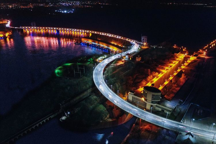 High angle view of illuminated bridge over city at night