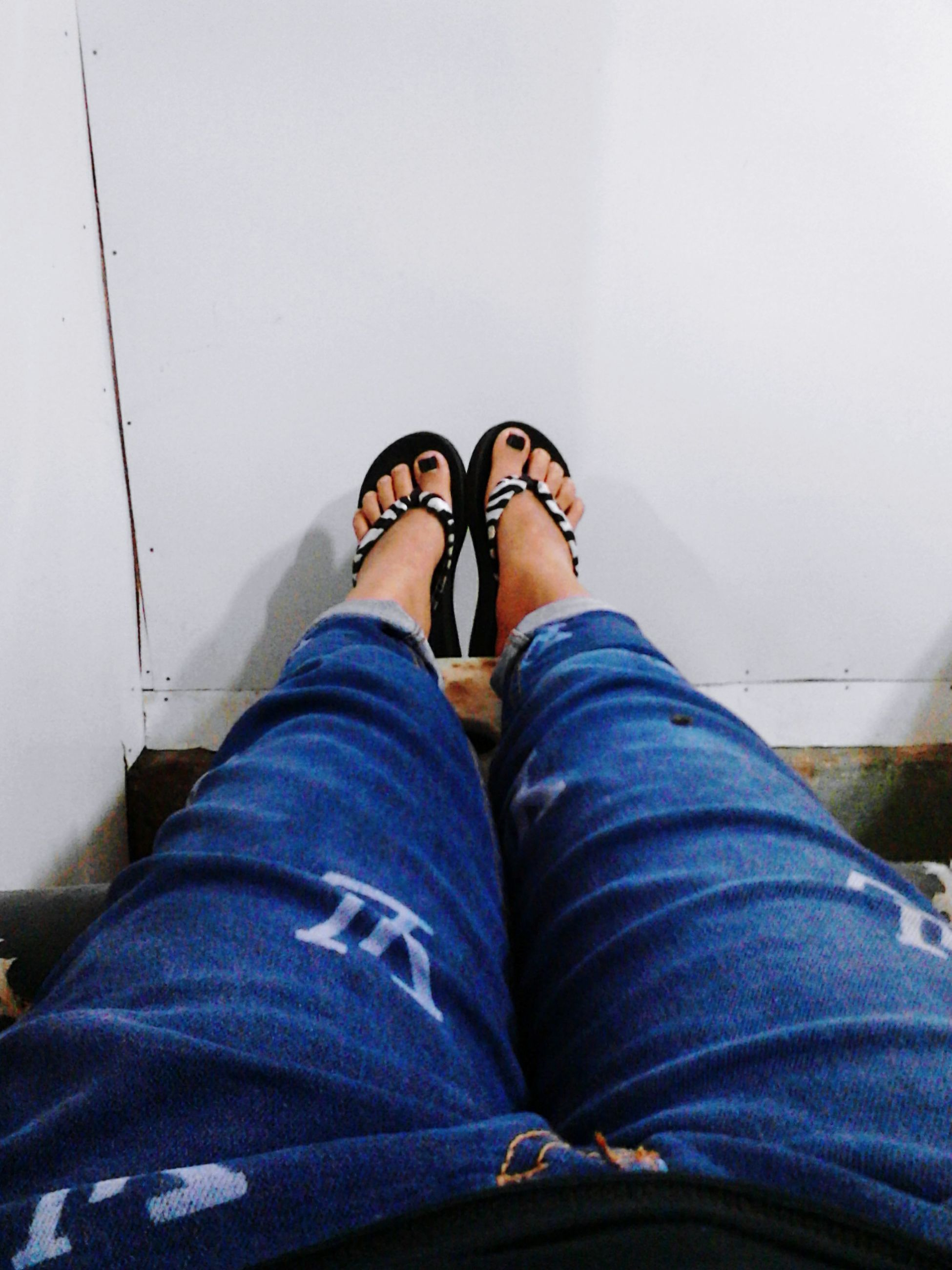 low section, person, shoe, personal perspective, jeans, lifestyles, human foot, relaxation, casual clothing, leisure activity, sitting, standing, footwear, indoors, legs crossed at ankle, men