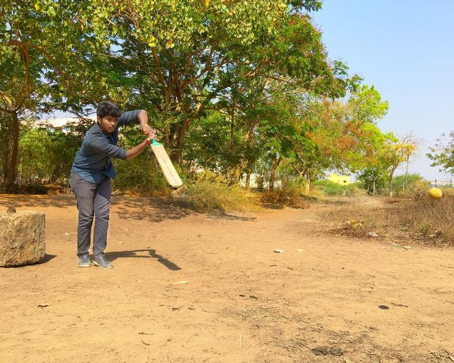 Ball Bat Cricket Field Playing Batting Cricket Match One Person Full Length Real People Men Lifestyles Leisure Activity Plant Nature Standing Day Tree Land Casual Clothing Males  Sunlight Front View Outdoors Growth Holding Mature Men Streetwise Photography The Art Of Street Photography