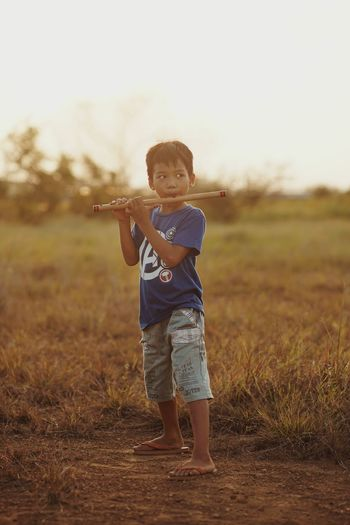 Full length of boy standing on field playing bamboo flute