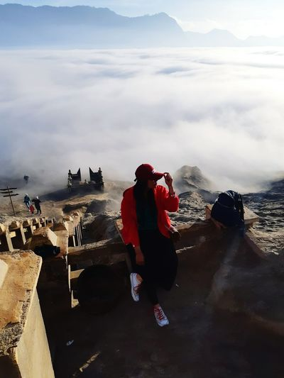 High angle view of mid adult woman sitting on mountain against cloudy sky