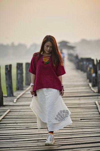 Full length of woman walking on footbridge against sky