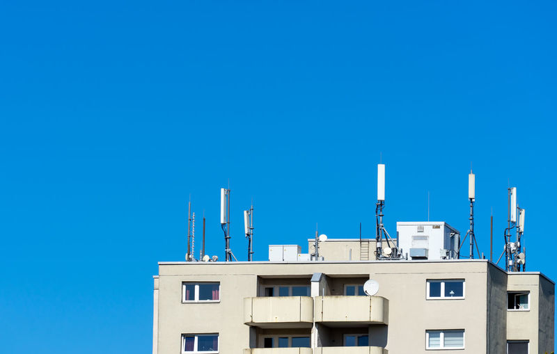 Low angle view of buildings with antennas against clear blue sky