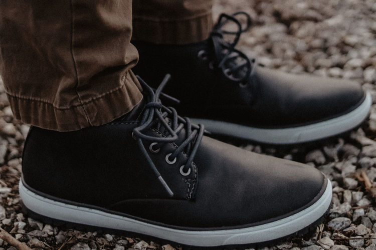 Low section of person wearing shoes on ground