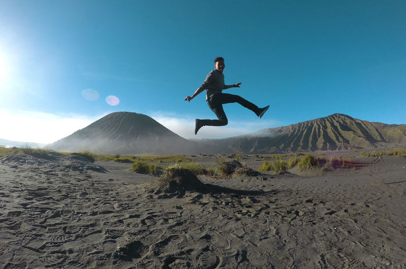 Young man jumping on mountain against clear sky