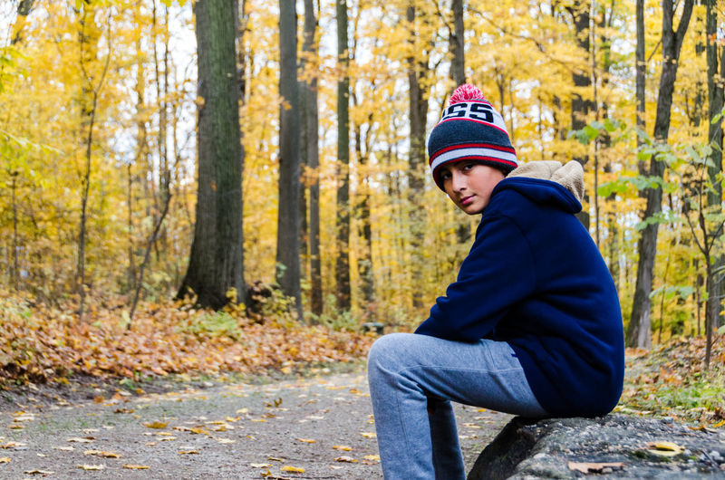 Portrait of smiling boy sitting in forest during autumn