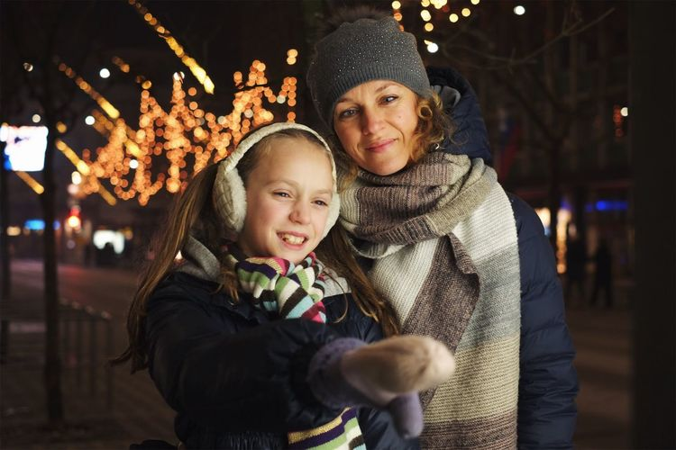 This holiday season is full of sparks. Looking At Camera Bonding Portrait Togetherness Waist Up Family With One Child Christmas Smiling Childhood Family Focus On Foreground Real People Knit Hat Warm Clothing Leisure Activity Happiness Young Women Cheerful Christmas Market Vacations City Life Magic Sparks Authentic Moments