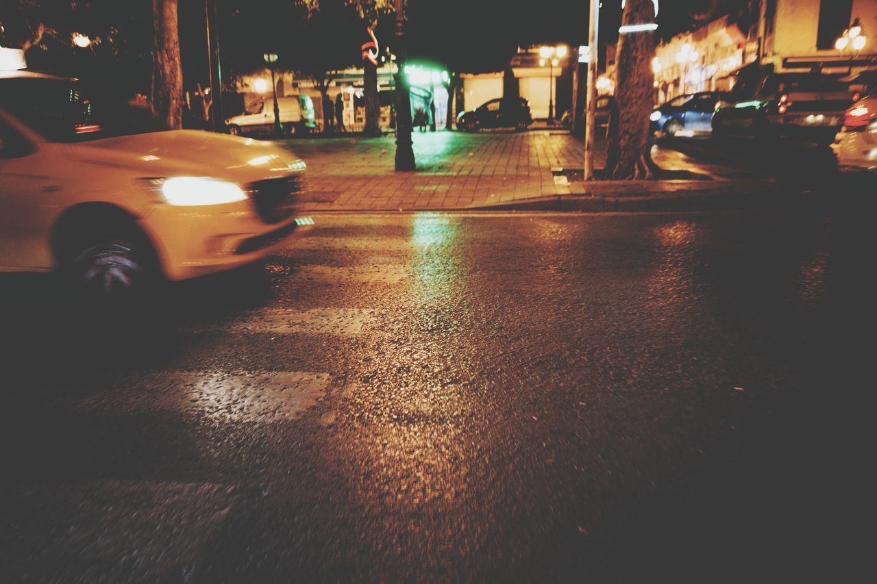 night, transportation, city, car, motor vehicle, illuminated, mode of transportation, street, land vehicle, road, architecture, rain, wet, city street, building exterior, headlight, built structure, no people, city life, rainy season
