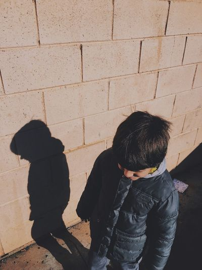 High angle view of boy standing against wall