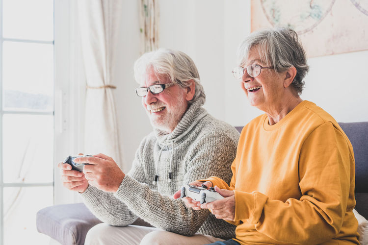 Man and woman playing video game at home