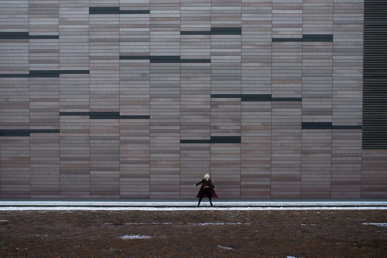Woman posing against industrial building