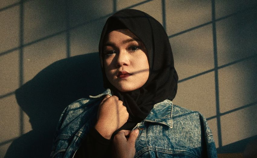 Portrait of young woman wearing hijab against wall during sunset